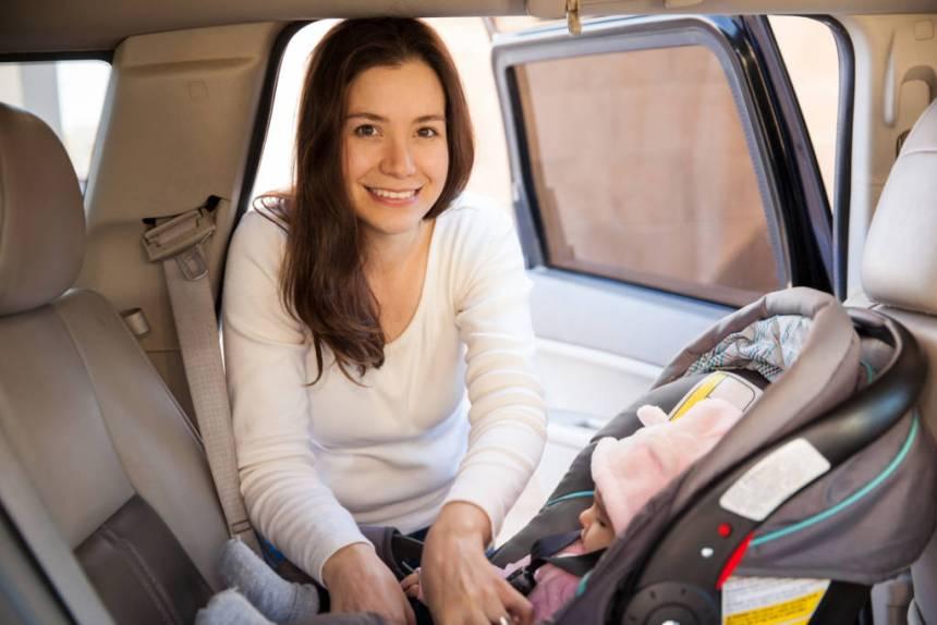 mom putting child in car seat