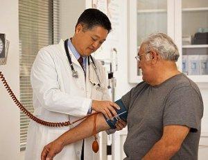 A doctor checks a man's blood pressure