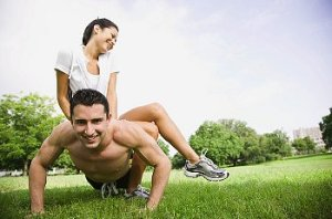 a man does push-ups while woman sits on his back