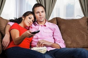 A couple watching TV and eating popcorn