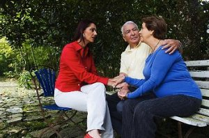 Woman speaks to elderly couple on an outside bench