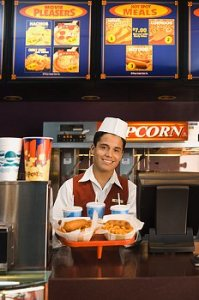 A fast food worker holds up a tray of fries and food.