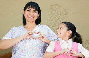 Mother and daughter make hand hearts over their hearts