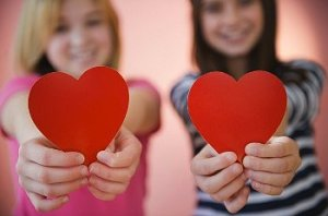 Young women hold up heart cut-outs