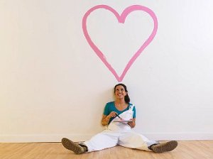 Woman in white overalls sits on the floor beneath a painted pink heart