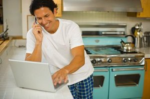 A man wearing pajamas while using his laptop in the kitchen