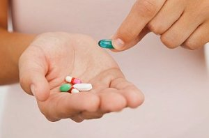 A woman holds a selection of pills in her hand and holds out a blue pill with the other