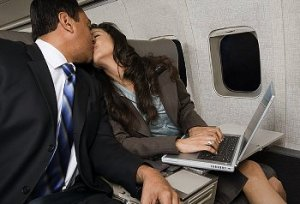 Two people in suits kiss on a plane in their seats