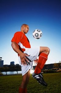 Soccer player juggles ball outdoors