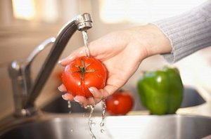 Woman washes a tomato in the sink