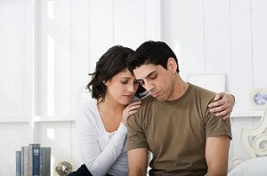 Distressed couple sit holding each other
