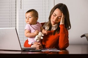 A businesswoman and mother holding her head in one hand and her baby in the other