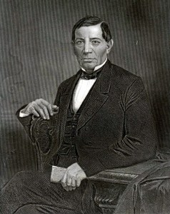 Benito Juarez sitting on a chair in a suite and bow tie