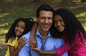 A man with two daughters with curly hair hug him for the camera