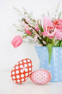 Two eggs lean on pink colorful potted plant