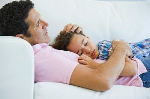 Father and daughter sleep on a white couch together