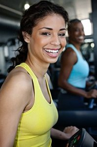 Two girls on treadmills smile at the camera