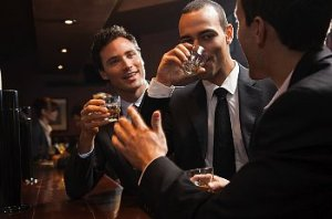 Three young men in suits drink at a bar.
