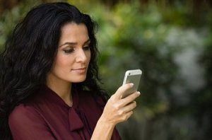 Woman with long black hair in a maroon blouse texting