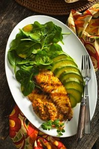 Fish with sliced avocado and greens