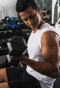 A muscular man lifts dumbbell for a bicep curl