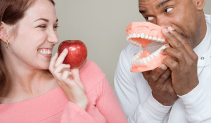 A dentist and his assistant holding an apple and a dental mold