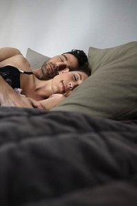 Couple sleeps in bed with gray sheets