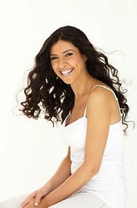 Woman with long hair smiles at camera wearing white camisole