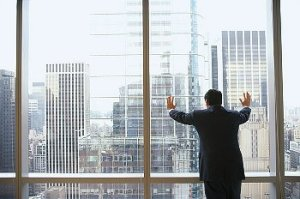 A man leans against a large office window