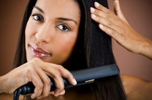 A woman straightens her hair while looking at the camera