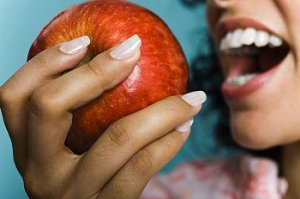 Woman about to take a bite out of an apple