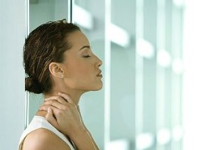 Woman leans back against white shelf in pain