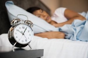 Alarm clock sits on a bed side table as woman sleeps