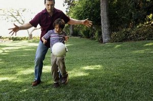 Father and son kick a soccer ball around in the park