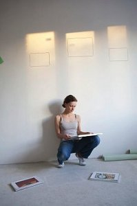 Woman in empty space looks at photos for wall
