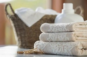 A laundry basket sitting next to fresh, folded towels