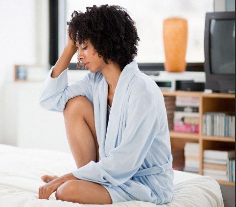 woman sitting holding head depressed