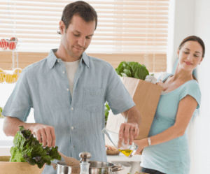 A husband cooking dinner while his wife holds grocery bag and watches him