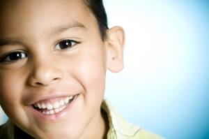 A little boy smiling against a blue background