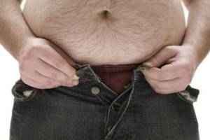 A man with a large belly trying to button his jeans