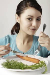 woman eating a carrot, skipping meals