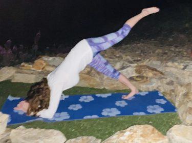 Parivrrta Ashta Chandrasana - high lunge with twist pose - yoga pose yoga at night girl wearing white long-sleeved shirt and purple pants