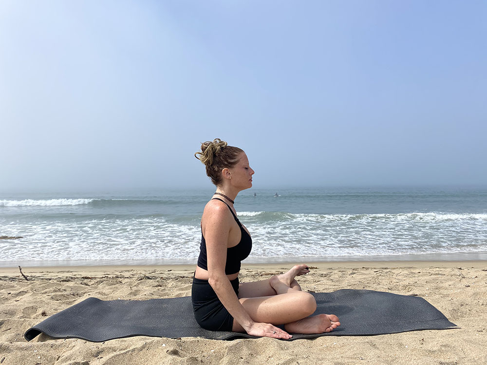 Agnistambhasana - fire log pose - yoga pose girl sunny day yoga on the beach