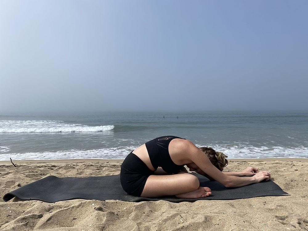 Agnistambhasana - fire log pose - yoga pose girl sunny day yoga on the beach