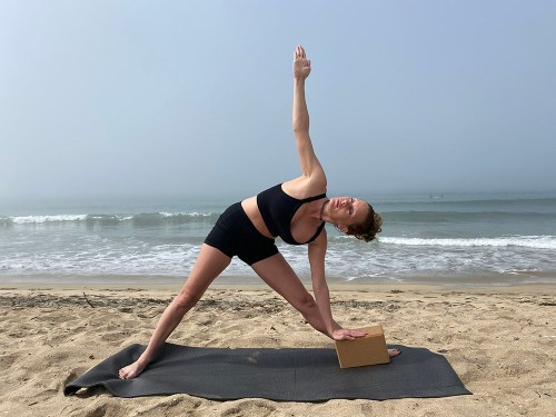Trikonasana - triangle pose with block - yoga pose girl sunny day yoga on the beach