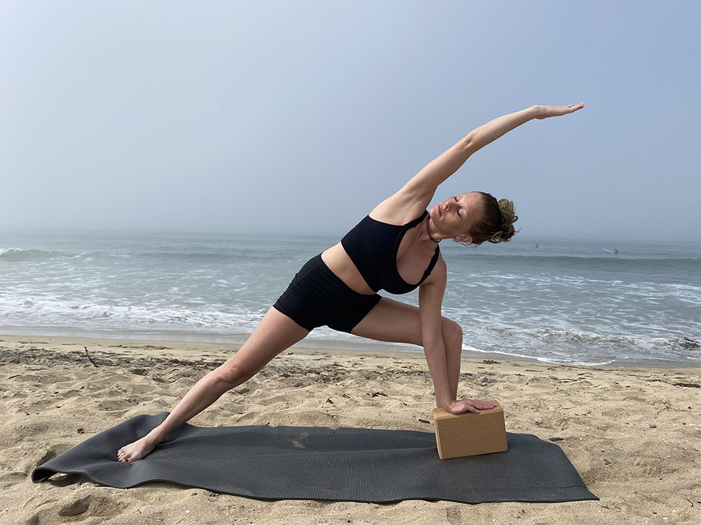 Utthita Parsvakonasana - extended side angle pose with block - yoga pose girl sunny day yoga on the beach