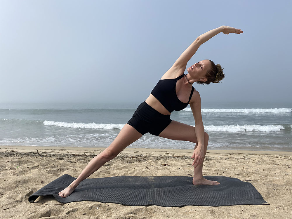 Utthita Parsvakonasana - beginner extended side angle pose - yoga pose girl sunny day yoga on the beach