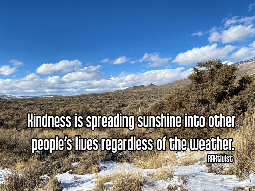 bright blue partly cloudy sky over high plains with distant low mountains dry brown field grass and shrubs with patch of white snow - ahimsa spreading kindness Quote: Kindness is spreading sunshine into other people's lives regardless of the weather. - RAKtivist