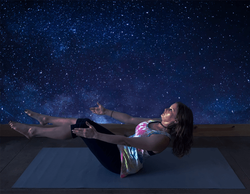 Ardha Navasana - half boat pose - yoga pose girl from side wearing tie dye shirt with cool purple and blue star background