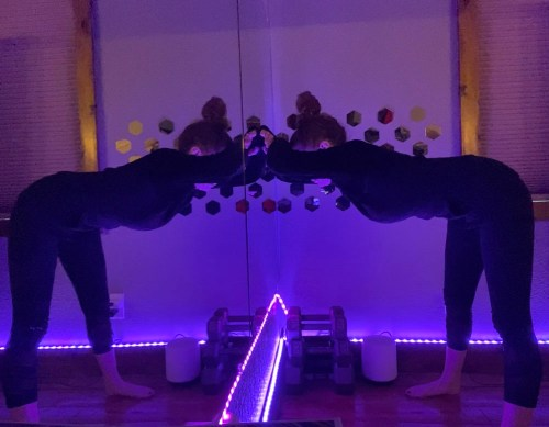 Temple Pose - beginner partner yoga pose - yoga pose yoga girl wearing black yoga set doing yoga inside in cool pink and purple yoga studio